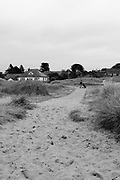 A sandy public footpath crosses between 18th fairway & 1st fairway. Looking towards houses in land from the coast, a golfer pass pushing his caddy.<br /> <br /> Photo by Jonathan J Fussell, COPYRIGHT 2021