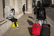As the UK government lead by Prime Minister Boris Johnson urges Britons to avoid non-essential travel to EU countries, and to avoind contact with others in public places like pubs and theatres during the Coronavirus pandemic, a masked traveller wearing blue surgical gloves pulls heavy baggage behind her through the capital's financial district, on 16th March 2020, in London, England.