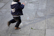 little child running after soap bubbles
