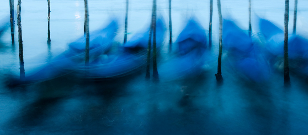 Moored gondolas moving under waves with long exposure on Grand Canal in Venice Italy