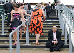 © licensed to London News Pictures. ASCOT, UK.  16/06/11. A man rests on a stairwell. Ladies Day at Royal Ascot 16 June 2011. Royal Ascot has established itself as a national institution and the centrepiece of the British social calendar as well as being a stage for the best racehorses in the world. Mandatory Credit Stephen Simpson/LNP