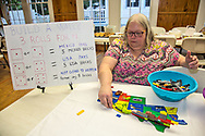"""Ann Porter Chair of the Democractic Executive Committiee offers people roles of the dice connected to buidling a wall during the """"Ear of Steve"""" fundraising  event in Abita Springs, LA on June 11."""
