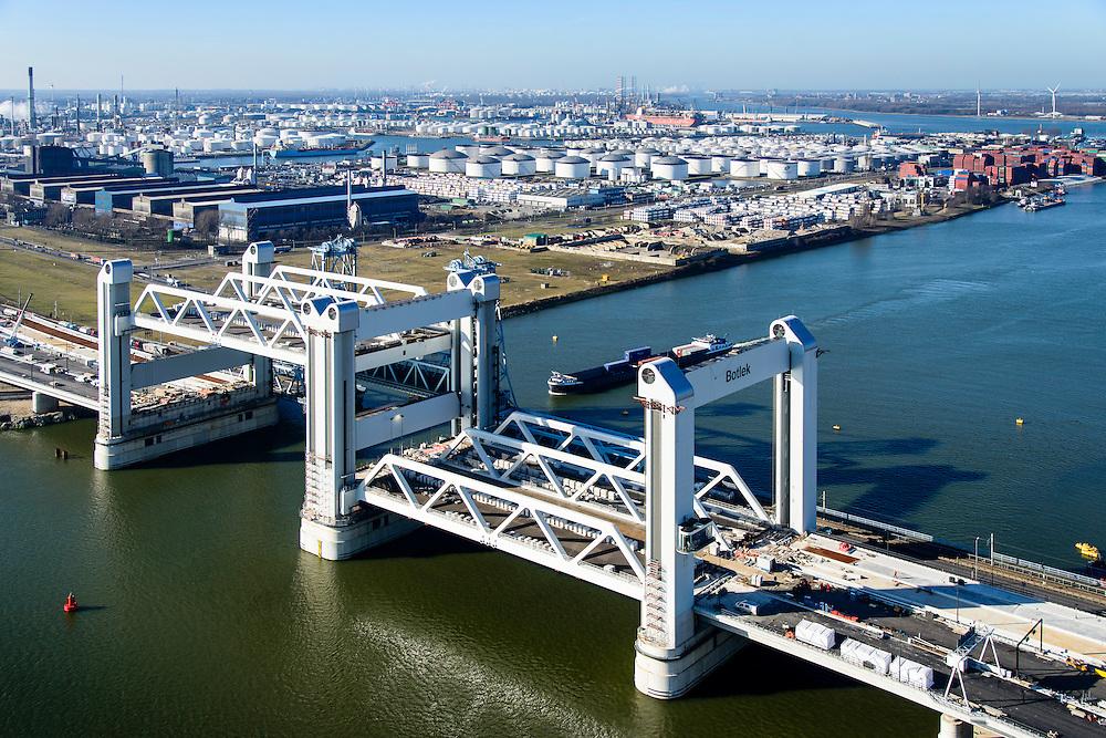 Nederland, Zuid-Holland, Rotterdam, 18-02-2015; bouw van de nieuwe Botlekbrug, binnenvaartschip passeert de nieuwe brug. De brug over de Oude Maas is een hefbrug, een van de twee brugdelen in geheven toestand. De heftorens van de oude brug gaan verscholen achter de nieuwe brug. <br /> Construction of the new Botlek bridge. The bridge over the Oude Maas is a vertical-lift bridge or lift bridge, one of the two bridge sections raised. <br /> luchtfoto (toeslag op standard tarieven);<br /> aerial photo (additional fee required);<br /> copyright foto/photo Siebe Swart