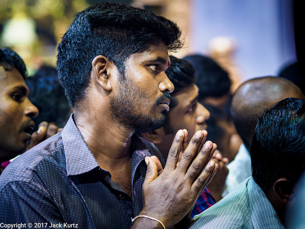 """09 JULY 2017 - SINGAPORE:  A Hindu man prays in Sri Veeramakaliamman Temple in Singapore's """"Little India."""" There are hundreds of thousands of guest workers from the Indian sub-continent in Singapore. Most work 5 ½ to six days per week. On Sundays, the normal day off, they come into Singapore's """"Little India"""" neighborhood to eat, drink, send money home, go to doctors and dentists and socialize. Most of the workers live in dormitory style housing far from central Singapore and Sunday is the only day they have away from their job sites. Most work in blue collar fields, like construction or as laborers.   PHOTO BY JACK KURTZ"""