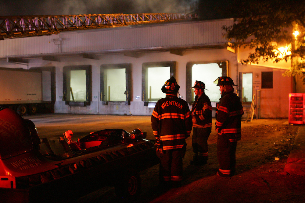 Mansfield, MA 09/13/2011.Firefighters look at the smoldering Miller Recycling plant as it burns on Tuesday night.  The 4 alarm fire brought firefighters from as far away as Canton and Rhode Island to the scene..Wicked Local Photo by Alex Jones