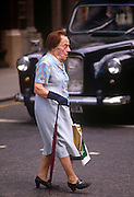 An elderly lady shopper walks over a pedestrian crossing in Bond Street, a retail street in central London. Making her way safely across the road, in front of a London taxi cab the woman uses an unmbrella to steady herself while holding some plastic shopping bags.