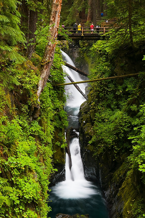 Hikers stand on the bridge for views of the dramatic Sol Duc Falls, Olympic National Park, Washington.