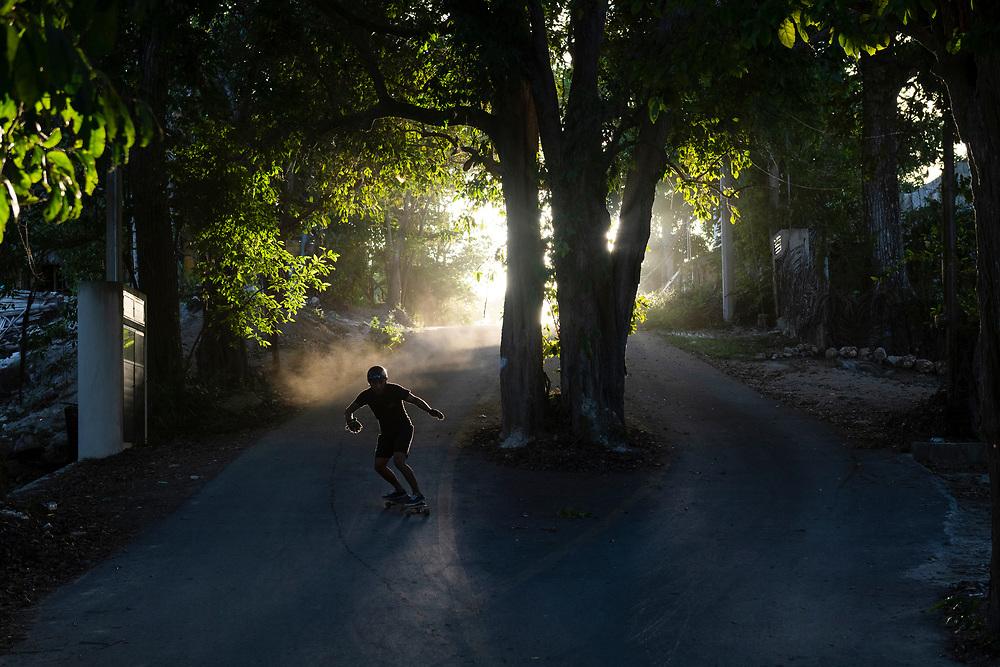 Bacalar, Mexico - June 3, 2021: Esahu Soto Rojas skateboards down a street in Bacalar.