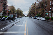 Brooklyn, NY - 18 April 2020. At noon on a Saturday, the normally busy Ocean Avenue at Avenue J is without traffic—one car in the far distance and a UPS truck making a delivery are the only signs of traffic.
