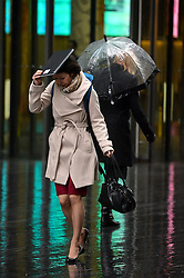 One woman uses a folder to keep the elements at bay. Londoners attempt to stay dry under umbrellas as strong winds and rain continue to affect the UK. <br /> Tuesday, 11th February 2014. Picture by Ben Stevens / i-Images