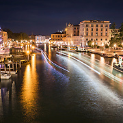 Venice, Italy and the Grand Canal  is one of the world's top travel destinations and lights up at night amid Italy's beautiful architecture. Gondolas, water taxis and buses navigate the canal at night leaving a trail of lights.