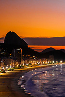 Overview of Avenida Atlantica and Copacabana Beach predawn, with Sugarloaf Mountain in background, Rio de Janeiro, Brazil.