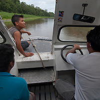 A boat navigates up the narrow Yanayacu River, a tributary of the Amazon River in Peru.