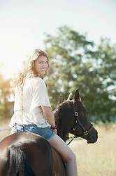Young woman riding a horse in farm looking over shoulder and smiling, Bavaria, Germany