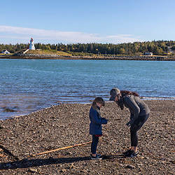 A woman and her daughter explore the shoreline in Lubec, Maine. Mullholland Point Light is across Lubec Narrows on Campobello Island.