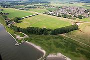 Nederland, Gelderland, Gemeente Rijnwaarden, 28-06-2006; luchtfoto (25% toeslag direkt naast - Westelijk - van het dorpje Pannerden ligt een overlaat die gebruikt wordt in geval van hoog water in de Rijn (hier genaamd: Pannerdensch Kanaal, links in de voorgrond een speciaal aangelegde dijk (halve cirkel met bomen in de voorgrond), dwingt het water naar de overlaat: de opening wordt geflankeerd door twee roestbruine damwanden; het gehele gebied naar linksboven kan dan onder water komen te staan, de weg in het midden (naar de veerpont) staat op pijlers; de overlaat wordt 'de groene rivier' genoemd door beheerder en eigenaar Rijkswaterstaat; het dorp en achterland worden beschermd door de Galgendaalse Dijk; ruimte voor de rivieren, watermanagement, wateroverlast, infrastructuur, ruimtelijke ordening.luchtfoto (toeslag aerial photo (additional fee required .foto Siebe Swart / photo Siebe Swart