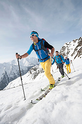 Three men skiing winter Alps cross-country