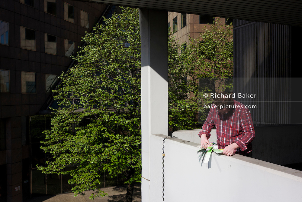 Surrounded by modernist architecture, a man sorts through a swatch of green pantones with green tree behind.