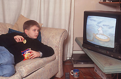 Young boy lying on sofa eating crisps and watching television,