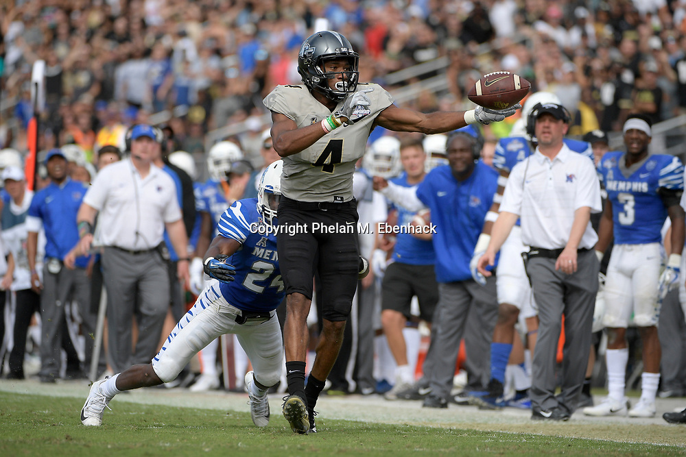 Central Florida wide receiver Tre'Quan Smith (4) drops a long pass in front of Memphis defensive back Tito Windham (24) during the first half of the American Athletic Conference championship NCAA college football game Saturday, Dec. 2, 2017, in Orlando, Fla. (Photo by Phelan M. Ebenhack)