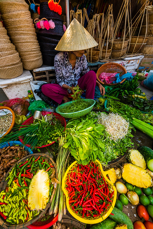Selling produce at outdoor market, Central Market, Hoi An, Vietnam.