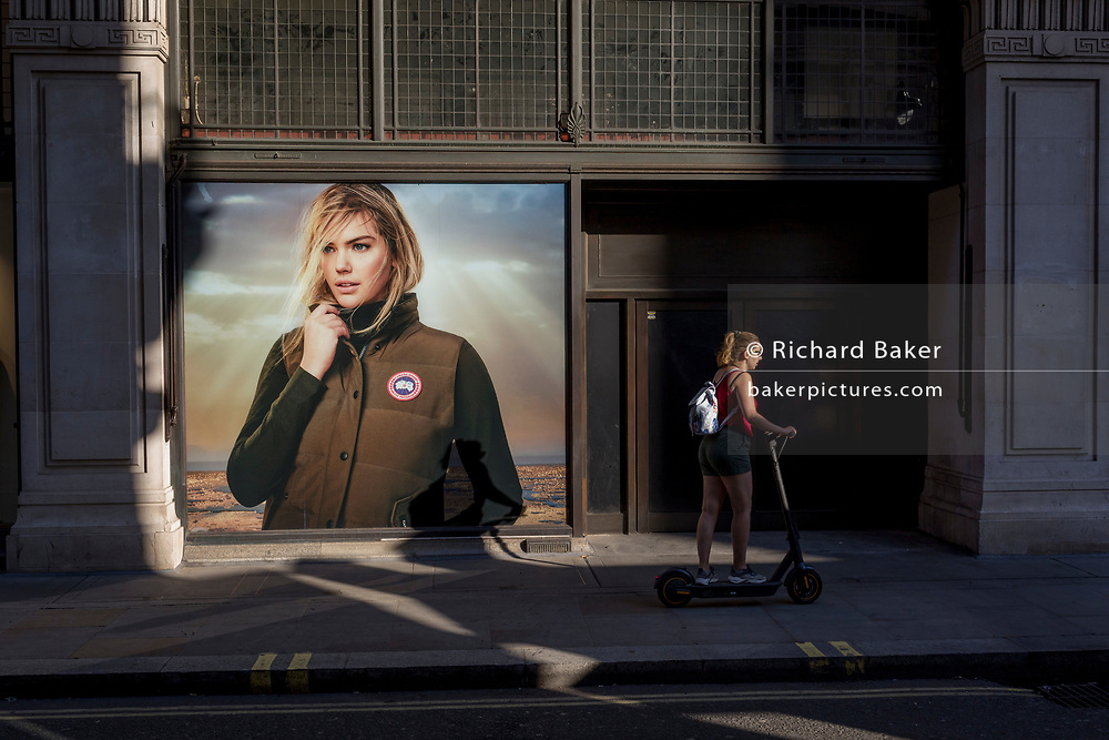 With a further 154 UK covid deaths reported in the last 24hrs, bringing the total to 43,081 victims during the Coronavirus pandemic, the easing of government lockdown restrictions for the re-opening of shops continues and a lady scoots past a billboard for Canada Goose on Little Argyll Street, on 24th June, in London, England.