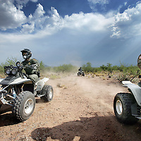 Verenigde Staten.Arizona.Nogales.juli 2005.<br /> Grenspolitie van Arizona verkennen de grens tussen de VS en Mexico in de buurt van grensstad Nogales op hun vierwielige motoren (Quads)  op zoek naar illegalen die vanuit Mexico de grens oversteken.<br /> Droogte.Grenscontrole.Hitte.Helm.border Patrol.Illegale vluchtelingen.Mexico.Mexicaan.Jagen.Jacht.Motor rijden.<br /> Archives 2005. Chase by police on illegal Mexicans who cross the border in Arizona.