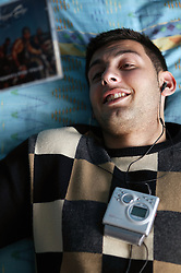 Young man lying on the bed listening to a mini disc player; model released for use in HIV and Aids,