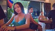 SEX INDUSTRY TOURISM. South East Asia, Cambodia, Phnom Penh. Taxi girls, prostitutes, serve foriegn tourists & Khmer, Cambodians. The sex industry is part of the fabric, servicing all classes of Cambodian society. Girls are forced into prostitution because of poverty and corruption that exists across the country. People might earn 1 to 2 $ per day, even less in rural areas, so the lure of prostitution is high. Families can sell young girls, virgins, for several hundred dollars. Cheap brothels line the streets in parts of the city centre, near railway tracks, and on the periphery. Sex for Cambodians at cheap prices in the street brothels, as low as 1 $ US, to exorbitant fees in penthouse hotel suites for the rich. Sex tourism industry attracts Western and Asian tourists typically paying 10 - 30 $ US. Expressions such as 'yam yam', eating, for a blowjob 'bam bam' for intercourse. There are 'lady-boys', youths, who use the money to pay for  sex change operations. Prostitutes spend lots of money on make-up, clothes, and mobile telephones. They live in squalor. Due to public advertising campaigns and outreach work, Aids and HIV cases have dramatically decreased, in Cambodia, since the late '90s. Condoms are encouraged, are cheap and widely available. This is seen as  a success story by medical and health authorities. There are risks as ex-prostitutes known as 'sweethearts' don't use condoms with their partners. Brothels, v & madams take their cut, but many taxi-girls work as free agents. Bars, pool halls or beer gardens have staff and taxi-girls available to service male clients, some work as barmaids or escorts. There is violence against prostitutes; gang-rape and murder by Khmer gangs. Once a girl has worked as a prostitute it is unlikely she can ever marry.///Taxi-girls waiting for clients at a pool bar