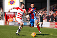 Doncaster Rovers midfielder Matty Blair (17) battles with Scunthorpe United midfielder Levi Sutton (22)  during the EFL Sky Bet League 1 match between Scunthorpe United and Doncaster Rovers at Glanford Park, Scunthorpe, England on 23 February 2019.