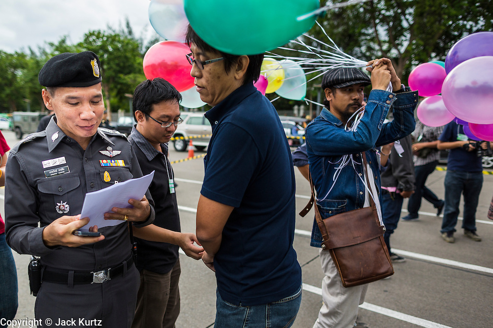 """24 JUNE 2014 - BANGKOK, THAILAND: A Thai police officer (left) talks to a poet  (right) about his poem after he read it aloud at a meeting of the Monsoon Poets Society in Bangkok. Members of the """"Monsoon Poets Society"""" gathered in front of the Anantasamakom Throne Hall Tuesday to pay homage to the People's Party, a Siamese (Thai) group of military and civil officers (which became a political party) that staged a bloodless coup against King Prajadhipok (Rama VII) and changed Thailand (then Siam) from an absolute monarchy to a constitutional monarchy on 24 June 1932. Since the coup against the civilian government on 22 May, the ruling junta has not allowed political gatherings. Although police read the poems, they did not arrest any of the poets or make any effort to break up the gathering.     PHOTO BY JACK KURTZ"""