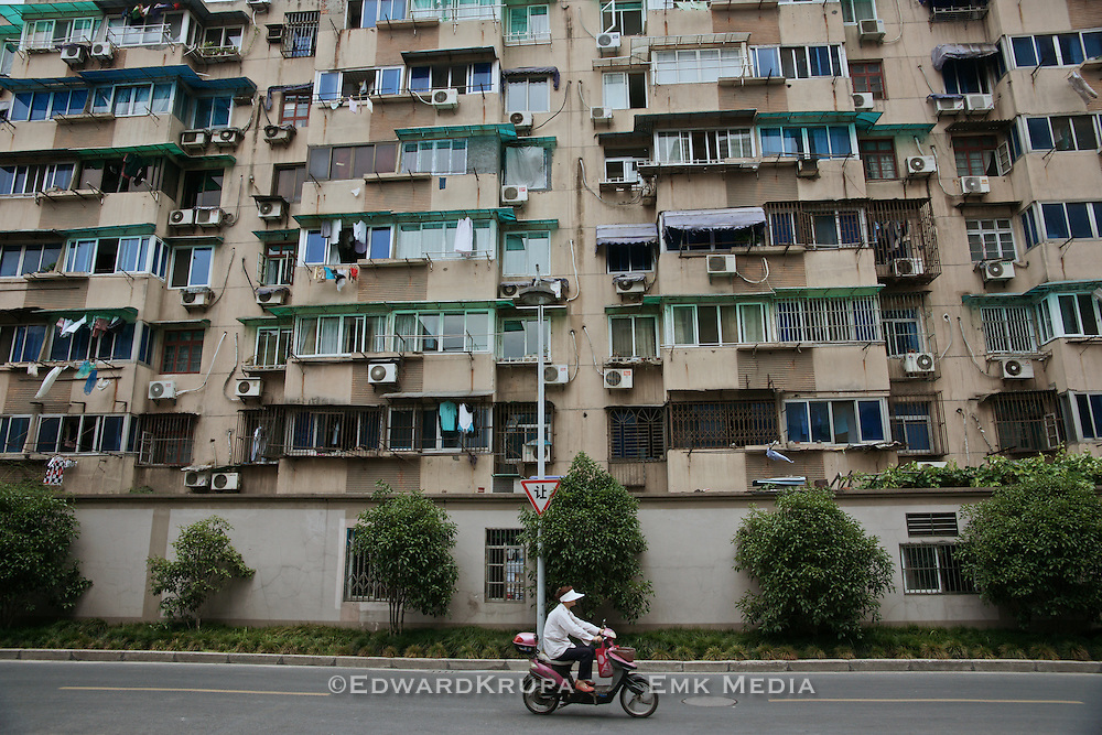 Woman riding by an apartment building in Hangzhou.