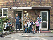 A young family outside their home in Cressingham Gardens on 25th May 2016 in South London, United Kingdom. Cressingham Gardens is a council garden estate, located on the southern edge of Brockwell Park. It comprises of 306 dwellings and built to the design of Lambeth Borough Council architect Edward Hollamby in the early 1970s. In 2012, Lambeth Council proposed regeneration of the estate, a decision highly opposed by many residents. Since the announcement, the highly motivated campaign group Save Cressingham Gardens has been active.