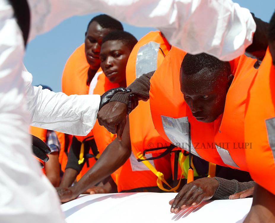 Migrants are helped to cross from their rubber dinghy to a Migrant Offshore Aid Station (MOAS) RHIB (Rigid-hulled inflatable boat) before  being taken to the MOAS ship MV Phoenix some 20 miles (32 kilometres) off the coast of Libya, August 3, 2015.  118 migrants were rescued from a rubber dinghy off Libya on Monday morning . The Phoenix, manned by personnel from international non-governmental organisations Medecins san Frontiere (MSF) and MOAS, is the first privately funded vessel to operate in the Mediterranean.<br /> REUTERS/Darrin Zammit Lupi <br /> MALTA OUT. NO COMMERCIAL OR EDITORIAL SALES IN MALTA