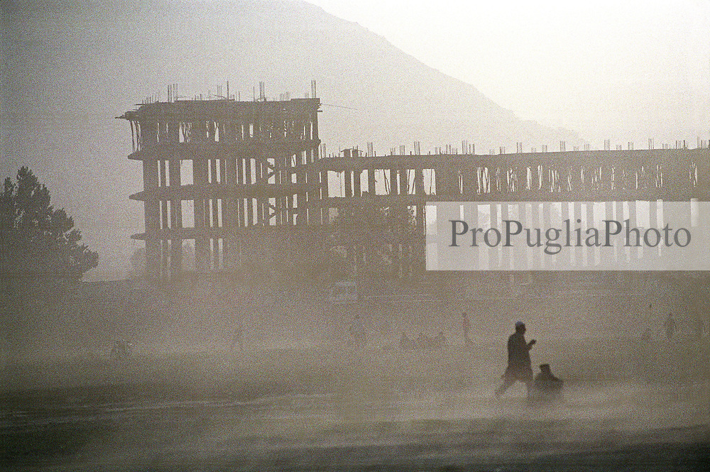 A dusty afternoon. In the backgrong a five-floor building under construction