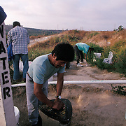 Migrants gather to wash their clothes in reclaimed water in the hills of northern San Diego, California where many make their homes amid the bushes and scrub brush. Please contact Todd Bigelow directly with your licensing requests. PLEASE CONTACT TODD BIGELOW DIRECTLY WITH YOUR LICENSING REQUEST. THANK YOU!