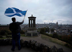 © Licensed to London News Pictures. 14/09/2014. Edinburgh, UK. A Yes campaigner waves the Saltire from the top of Calton Hill, Edinburgh, with the city and the Dugald Stewart Monument in the foreground. Photo credit: Isabel Infantes / LNP