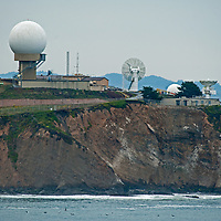 Radar & other communication equipment rises above the Pacific Coast at Pillar Point Air Forces Station by El Granada, California.