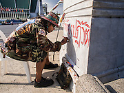 28 NOVEMBER 2013 - BANGKOK, THAILAND: An anti-government protestor puts graffiti on a wall that prevents protestors from reaching government offices in the Dusit section of Bangkok.   Protestors opposed to the government of Thai Prime Minister Yingluck Shinawatra spread out through Bangkok this week. Protestors have taken over the Ministry of Finance, Ministry of Sports and Tourism, Ministry of the Interior and other smaller ministries. The protestors are demanding the Prime Minister resign, the Prime Minister said she will not step down. This is the worst political turmoil in Thailand since 2010 when 90 civilians were killed in an army crackdown against Red Shirt protestors. The Pheu Thai party, supported by the Red Shirts, won the 2011 election and now govern. The protestors demanding the Prime Minister step down are related to the Yellow Shirt protestors that closed airports in Thailand in 2008.     PHOTO BY JACK KURTZ