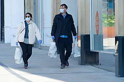 ©Licensed to London News Pictures 27/03/2020  <br /> Bromley, UK.A couple wearing masks, Bromley high street, South East London. The Prime Minister Boris Johnson has asked people to stay at home to help in the fight against Covid-19 and to only go out for essential reasons. credit:Grant Falvey/LNP
