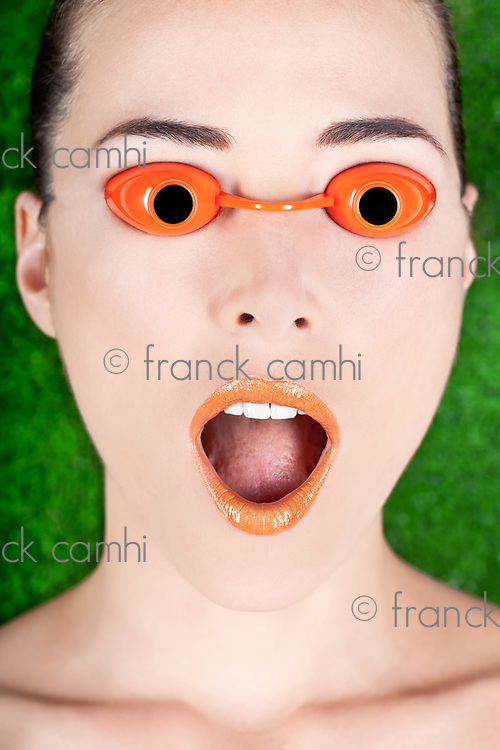 Closeup portrait of a surprised beautiful woman wearing tanning bed glasses with mouth open