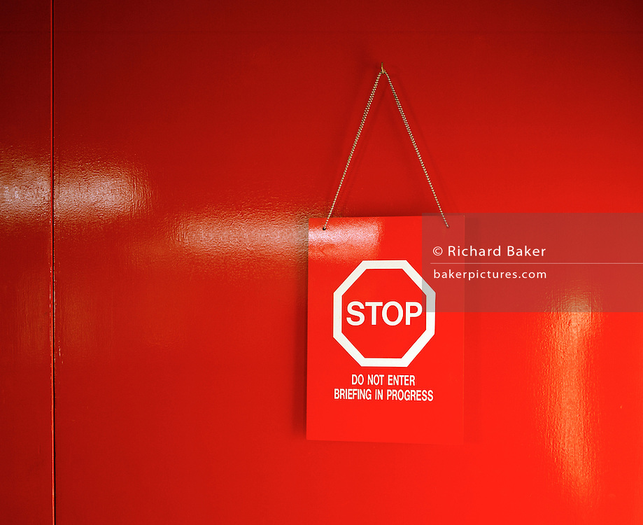 """A door painted with a high-gloss red finish is closed and a warning sign for privacy is hung to deter outsiders from entering. This briefing room belongs to the elite 'Red Arrows', Britain's prestigious Royal Air Force aerobatic team Lincolnshire, who use these offices as headquarters and administrative centre for the 90-plus displays they perform a year. The pilots' crew room is screened off from visitors and the notice says """"Stop, do not enter, briefing in progress"""" to isolate the serious business of briefing and de-briefing. Performance appraisals before and after a training flight or air show displays are intense. Matters of safety and perfection are discussed so the aviators politely close the door unless visitors have been invited in to hear about the features of the next flight or afterwards, the gentlemanly exchanges providing analysis and frank views."""