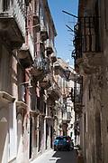 Street scene small city car driving along ornate alleyway Via Dione in Ortigia, Syracuse, Sicily