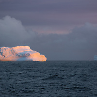 'Fade' – Crystal Sound, Antarctica<br /> <br /> The sun rays hit the waterline and light up these blocky, pinnacled and wedged icebergs as the seas grow rougher in Crystal Sound from exposure to the open Antarctic Ocean to the west.