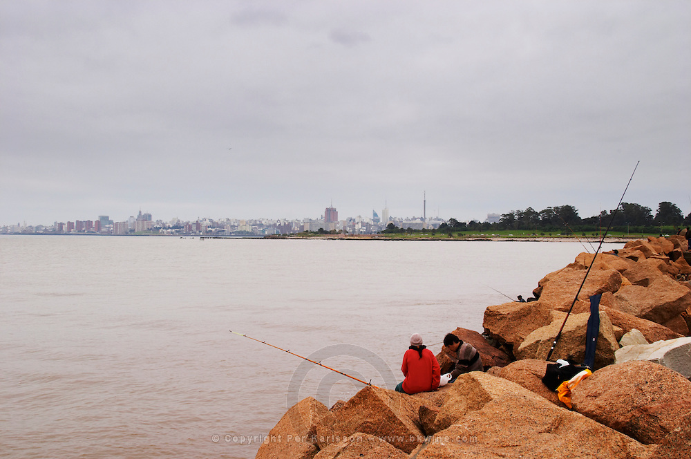 People sitting on big stone blocks along the river Rio de la Plata fishing with fishing rods and a view of the city skyline in the background on a grey and overcast winter day. Montevideo, Uruguay, South America