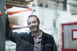 Portrait of a young male engineer in technology space and smiling, Freiburg Im Breisgau, Baden-Wuerttemberg, Germany