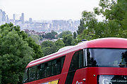 With the city in the distance, a Go Ahead London bus climbs up Sydenham Hill, on 15th June 2021, in south London, England.