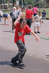 Primary school boy running in relay race; holding leaking beaker of water above his head; during P,E, lesson,