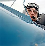 Close up portrait of 60's man in cockpit of vintage plane.