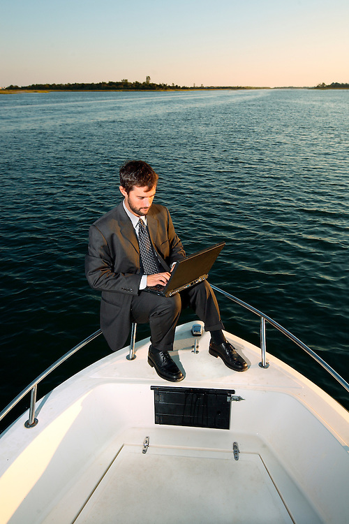 A business man works on his laptop on the bow of a boat, on the Intercoastal Waterway, in Wrightsville Beach, NC.